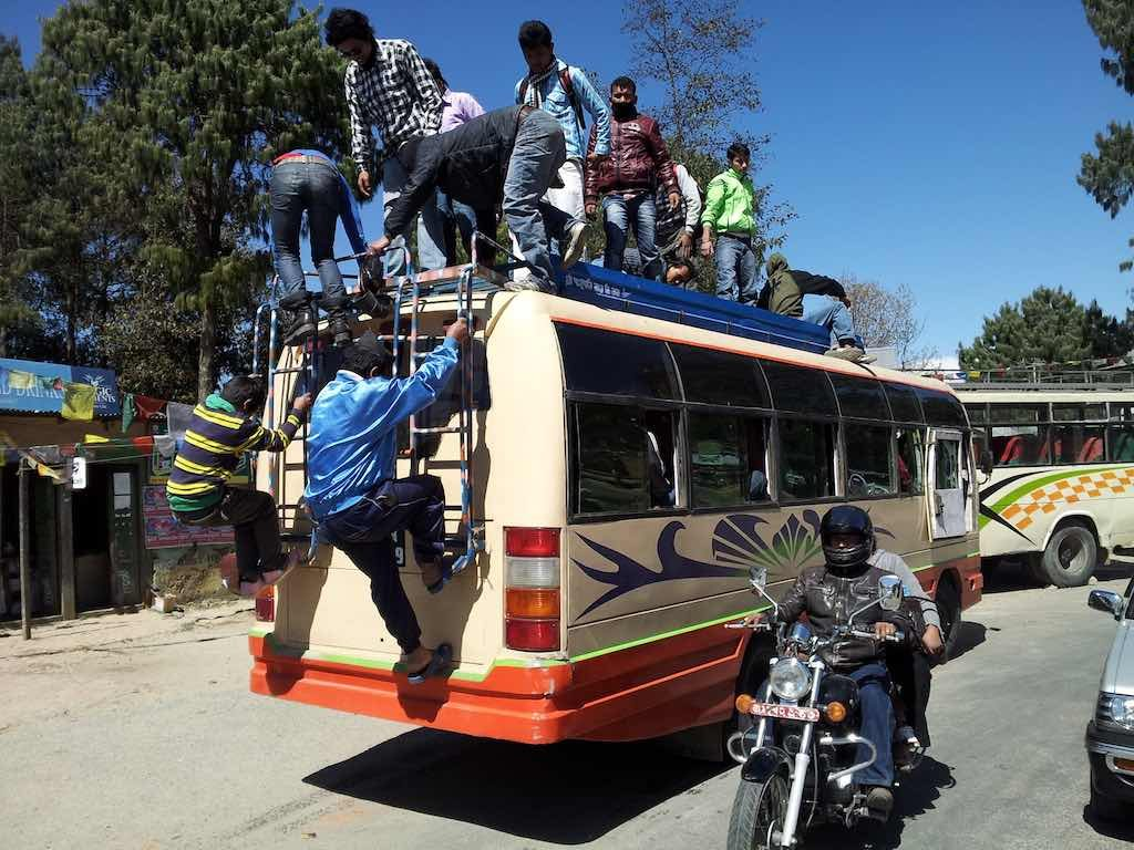 Nagarkot, Nepal - Men alighting from the top of the bus in Nagarkot