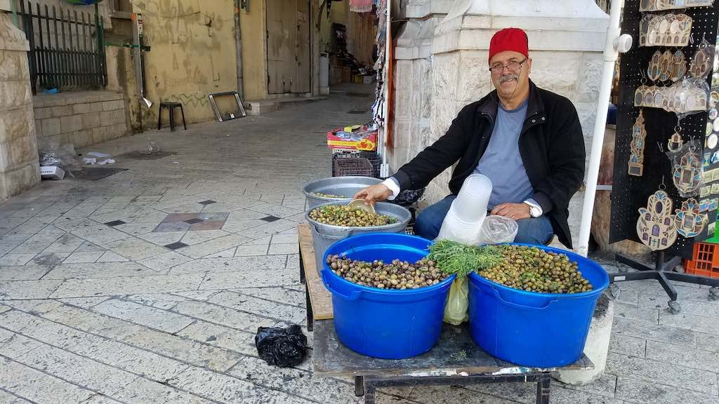 Nazareth, Israel - Olive Vendor. You can taste up to 13 olives, but the 14th you have to buy. But you must return the pits to a container near him.