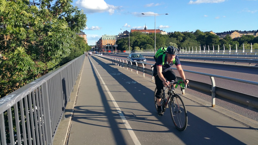Langholmen, Stockholm, Sweden - local riding a bike across the Vasterbron bridge